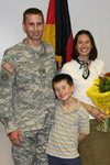 A Soldier receives an award with his family standing by his side.